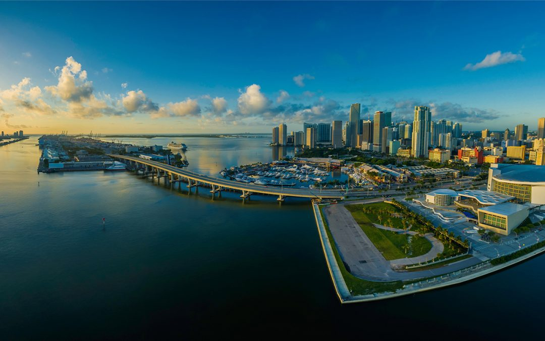 Aerial view of Brickell and the Port of Miami with a dramatic sunrise in the background.